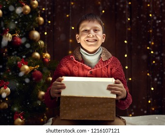 child boy sitting with gift box near christmas decorated fir tree, dark wooden background