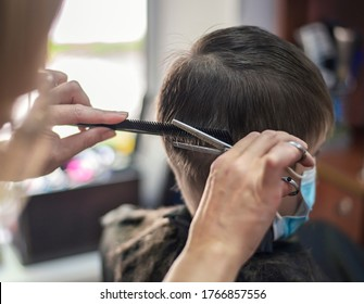 Child boy sitting in a mask at the hairdresser cutting a haircut.