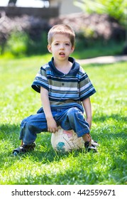 child boy sitting on a  ball in a grass outdoor