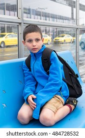 Child boy sitting on a bench in front of airport building, yellow taxi in the background, travelling with children concept.