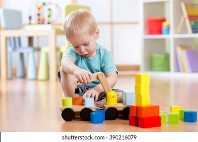 Child boy sitting on the floor and plays with building blocks and car