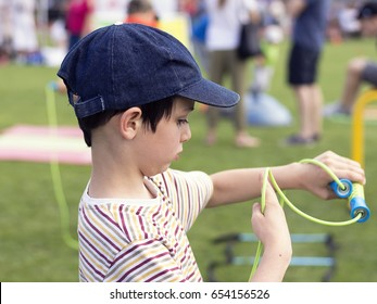 Child boy with skipping rope at school sport day.