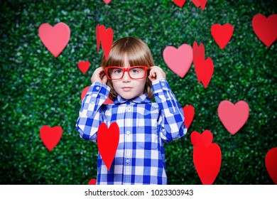 Ð¡ute child boy surrounded by hearts over lawny background. First love. Valentine's Day.