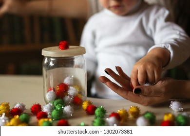 child boy Toddler puts colorful soft balls of toys in a jar, the development of fine motor skills. Previously, the development of the child at home in the real interior.