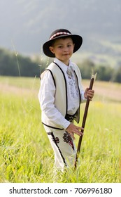 Child boy in traditional goral dress, hat and axe stands on meadow in Polish mountains. Vertical portrait with shallow depth of field