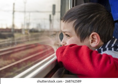 Child boy traveling by train and looking from a window.