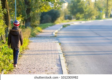 Child boy walking alone on a sidewalk