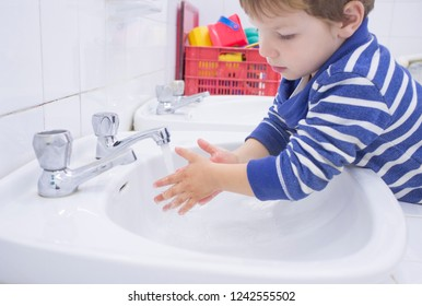 Child boy washing hands at adapted school sink. Learning hygiene habits