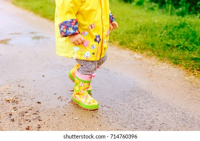 A child in bright clothes walks through puddles. Kind of bright yellow boots in the rain in autumn.