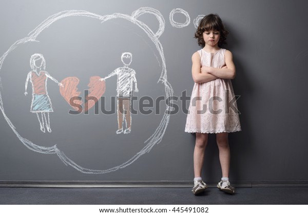 Child with the broken heart. Little girl crossed her hands and looks very unhappy. Depicted divorce of the parents on the grey wall with chalk. Kid suffers after the divorcement.