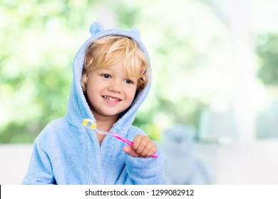 07a1fee2cc Child brushing teeth. Kids tooth brush and paste. Little baby in blue bath  robe