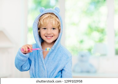 Child brushing teeth. Kids tooth brush and paste. Little baby in blue bath robe or towel brushing his teeth in white bathroom with window on sunny morning. Dental hygiene and heath for children.