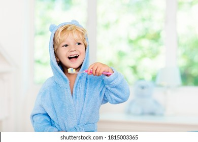 Child brushing teeth. Kids tooth brush and paste. Little baby boy in blue bath robe or towel brushing his teeth in white bathroom with window on sunny morning. Dental hygiene and heath for children. - Shutterstock ID 1815003365
