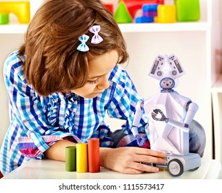 Child build robot toy. Kid engaged in robotics in programming classes. Girl is programming own tech smart toys with artificial intelligence at school.