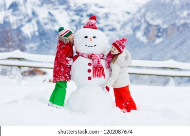 Child building snowman. Kids build snow man. Boy and girl playing outdoors on snowy winter day. Outdoor family fun on Christmas vacation in the mountains. Children play in Swiss mountain landscape.