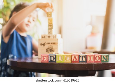 Child building wood blocks at playground. Girl kid playing stacking english alphabet wood blocks for practice language in school . Wood block education word on table. Children's education concept.
