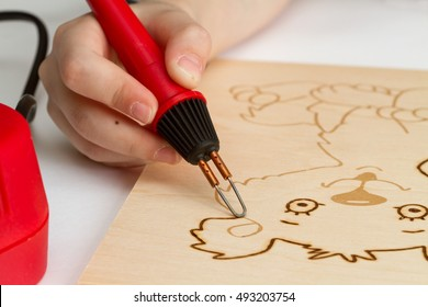 Child burns wood pattern by pyrography