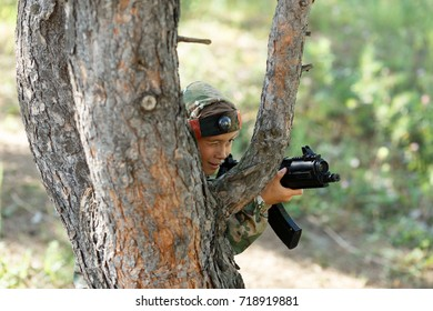 Child in camouflage with a gun shoots, laser tag in the forest. Lasertag shooting game. Military sport