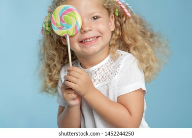Child and candy. A little girl is holding candy in her hands.