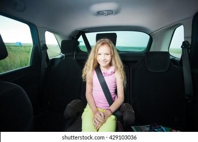 Child in car. Happy girl wearing seatbelts