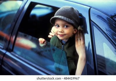 Child in car leaving, reaching to say goodbye