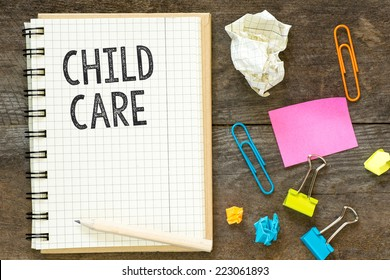 Child care. Child care on notebook crossed paper. Workspace mess: paperclips, stickers, crumpled paper. On wooden table