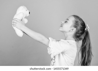 Child care. Sweet childhood. Childhood concept. Lovely small girl smiling happy face with favorite toy. Best friends. Happy childhood. Imaginary friend. Little girl play with soft toy teddy bear.