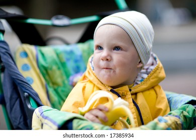 child in the carriage eating banana