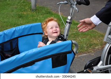 Child in carrier bicycle says goodbye to daddy