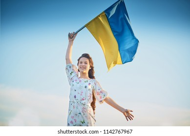 Child carries fluttering blue and yellow flag of Ukraine in field. Ukraine's Independence Day. Flag Day. Blue sky