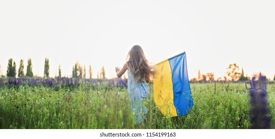 Child carries fluttering blue and yellow flag of Ukraine in lupine field. Ukraine's Independence Day. Flag Day