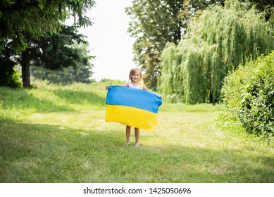 Child carries fluttering blue and yellow flag of Ukraine in field. Ukraine's Independence Day. Flag Day. Constitution day. Girl in traditional embroidery with flag of Ukraine