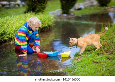 Child and cat playing with paper boat in puddle. Kids play outdoor by autumn rain. Little boy and his pet animal. Fall rainy weather outdoors activity for young children. Kid jumping in muddy puddles