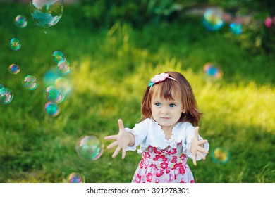 child catches soap bubbles