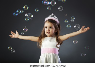 Child catching bubbles dressed like a princess