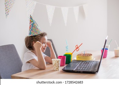Child celebrates birthday online. Videoconference holiday greetings. Cake decoration. Social distance self-isolation stay home. Video call laptop computer gadget. Baby boy kid european alone single