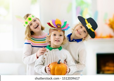 Child celebrating Thanksgiving. Kid in paper turkey hat, native American and pilgrim costume. Autumn fun crafts and art. Little boy and girl in decorated living room. Fall season pumpkin decoration.