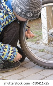 Child checking the tire on a bicycle or bike.
