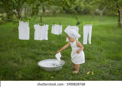 A child cheerfully laundered his clothes in the basin. Girl in white dress hanging wet laundry to dry. Washing in a vintage basin. Hand wash. soap powder. Laundry conditioner. Snow-white underwear