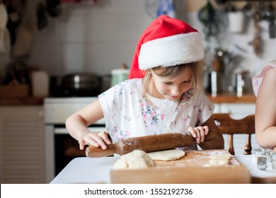 Child chef is cooking Christmas cookies in cozy home kitchen. Happy kids roll out dough with rolling pin. Girls are baking Xmas biscuits. Lifestyle moments.