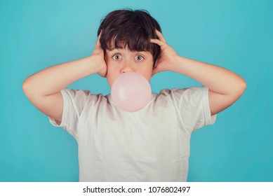 child with chewing gum in your mouth on blue background