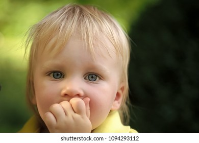 Child Childhood Children Happiness Concept. Baby infant with blue eyes on cute face and blond hair on natural environment. Child, childhood, family. Innocence, infancy, future concept