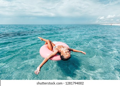 Child chilling on lilo in the sea water. Girl relaxing on inflatable ring on the beach. Summer vacations, idyllic scene.