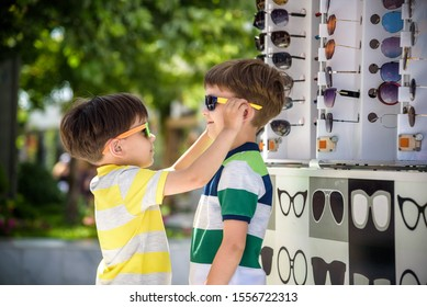 A child and a choice of sunglasses. Two little boys are standing in sun-proof glasses against the background of a shop window with glasses. Sunglasses sale during summer vocation.