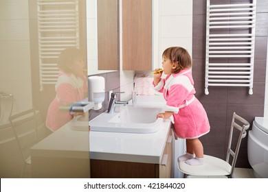 Child cleaning teeth in bathroom.