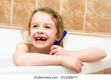 Child cleaning teeth , loosing primary tooth