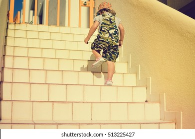 Child climb up staircase background. Back view image