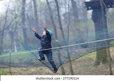 Child climbing into a net at outdoor playground