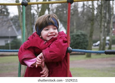 child in climbing rope - red, blue and green