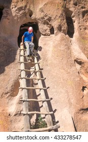 A child climbs the ladder out of the cave. This Cavate, called Cave Kiva. Bandelier National Monument, New Mexico, USA